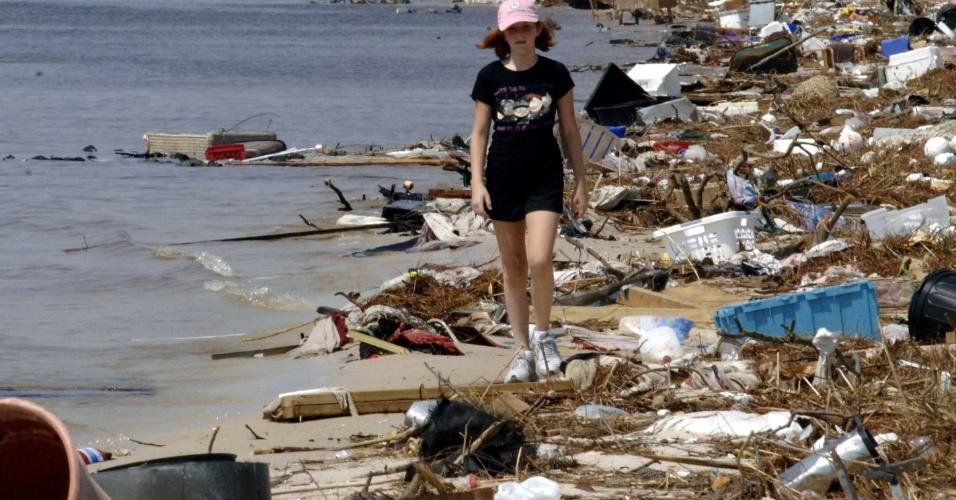 2.set.2005 - Mulher caminha por praia de Biloxi (EUA) devastada pelo furacão Katrina