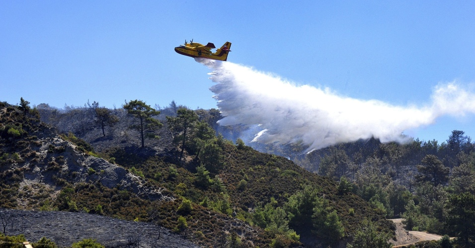 29.ago.2012 - Avião joga água nesta quarta-feira (29), em área afetada desde ontem por incêndio na ilha grega de Rodas