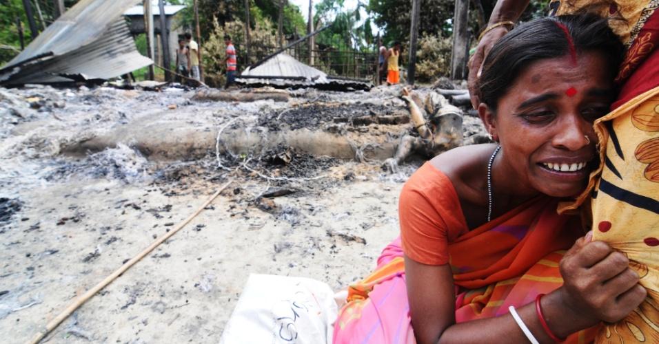 29.ago.2012 - Indiana chora próxima aos destroços de sua casa, que foi queimada por desordeiros nesta quarta-feira (29), na vila de Kharabari Charak Math, na Índia