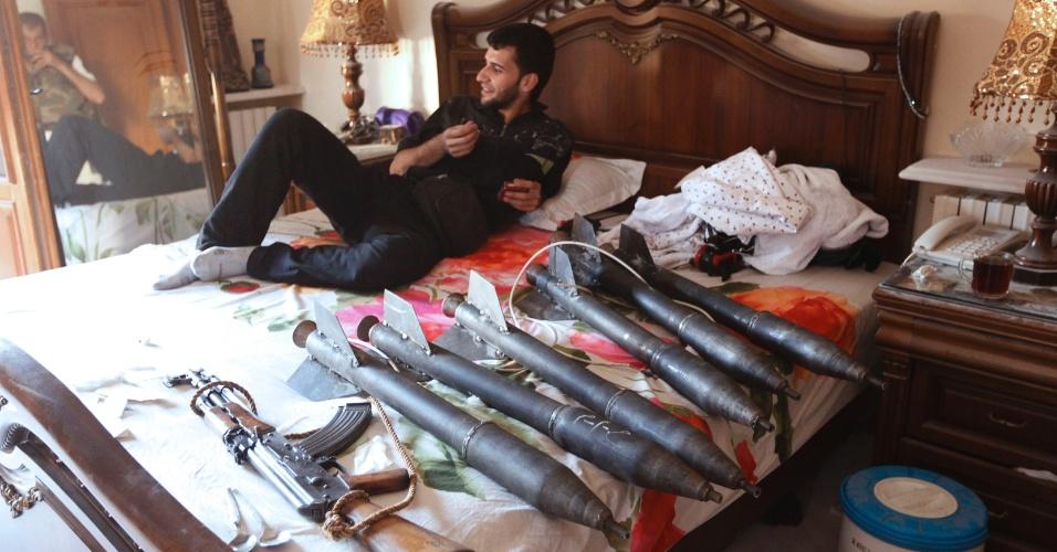 29.ago.2012 - Integrante das forças rebeldes da Síria descansa em cama ao lado de armamento utilizado no conflito contra o exército sírio em Aleppo, na Síria
