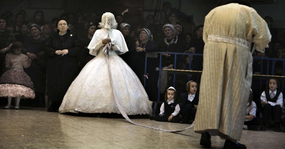 29.ago.2012 - Noiva judia dança com o avô, rabino de grupo ultra-ortodoxo, durante seu casamento em Mea Shearim, em Jerusalém