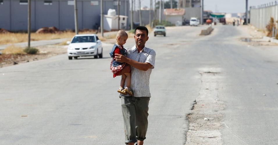 29.ago.2012. Homem caminha com criança no abrigo para refugiados de Bab al-Salam, na fronteira de Azaz, na Síria, com a Turquia. Nesta quarta-feira (29), o ministro de Relações Exteriores turco, Ahmet Davutoglu, pediu à ONU que cuide dos refugiados sírios dentro da própria Síria, em vez de deixá-los entrar em larga escala na Turquia, que já abriga mais de 80.000 refugiados