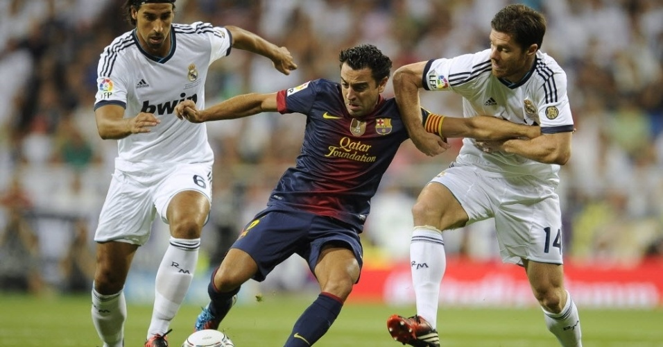 Xavi tenta passar pela forte marcação de Khedira (e) e Xabi Alonso (d), no primeiro tempo