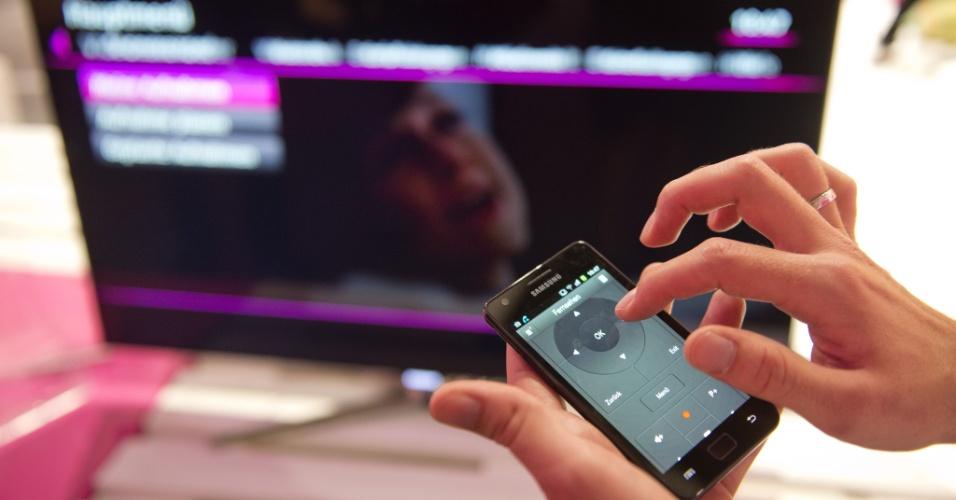 30.ago.2012 - Funcionário da Deustche Telekom (operadora de telefonia alemã) usa smartphone para controlar televisão no estande da companhia na IFA 2012. O evento reúne mais de 1,4 mil expositores e promete para a edição deste ano computadores com tela sensível ao toque, televisores 3D e dispositivos interconectados