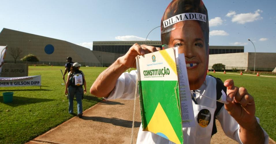 30.ago.2012 - Servidor do judiciário usa máscara da presidente Dilma Rousseff em protesto contra o ministro do Superior Tribunal de Justiça (STJ), Ari Pargendler, que participou das negociações com governo para o fim da paralisação. Os manifestantes lavaram a calçada e a placa do STJ com sabão e sal grosso