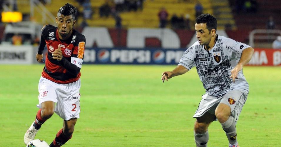 Leonardo Moura, lateral direito do Flamengo, conduz a bola marcado por jogador do Sport