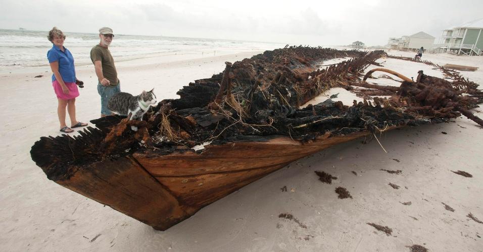 """1º.set.2012 - O casal de americanos Rhonda Hill e Scott Vanlin, acompanhado de um gato de estimação observam barco destruído em praia, após passagem do furacão """"Isaac"""" por Fort Morgan, no estado americano do Alabama"""