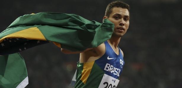 Alan Fonteles, abraçado com a bandeira do Brasil, comemora a vitória nos 200 m rasos T44