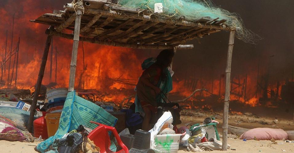 Mulher leva os pertences para um local seguro depois de um incêndio atingir uma favela em Chennai, Índia, neste domingo (2). De acordo com as autoridades locais, uma pessoa morreu e mais de 100 residências foram queimadas. A causa do incêndio ainda é desconhecida