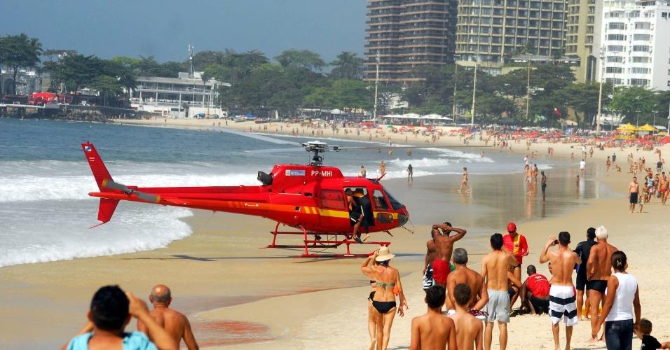 O corpo de bombeiros utiliza um helicóptero para socorrer uma vítima de afogamento na praia de Copacabana, zona sul do Rio de Janeiro, neste domingo (2).
