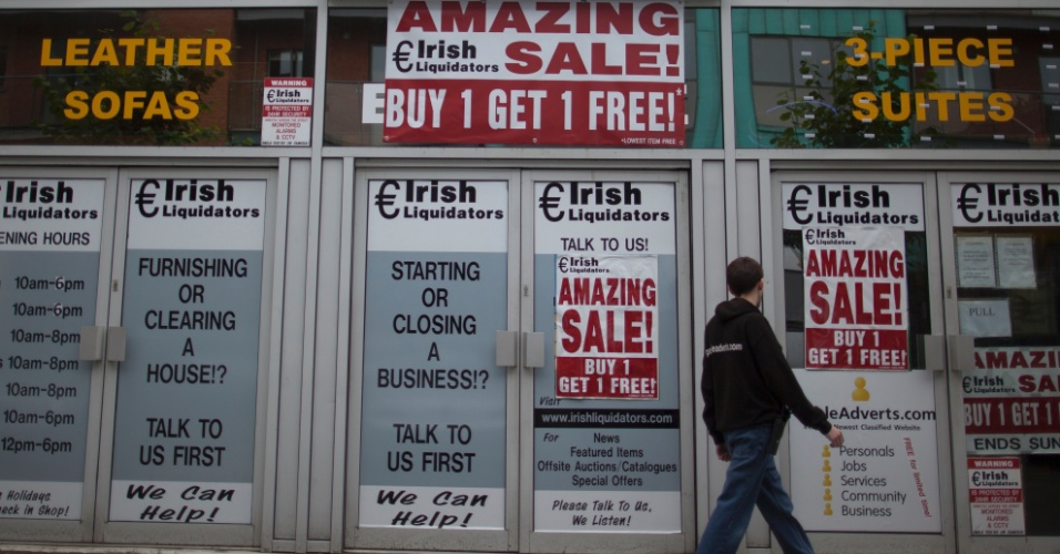 3.set.2012 - Homem caminha em frente a loja que vende itens para imóveis em Dublin