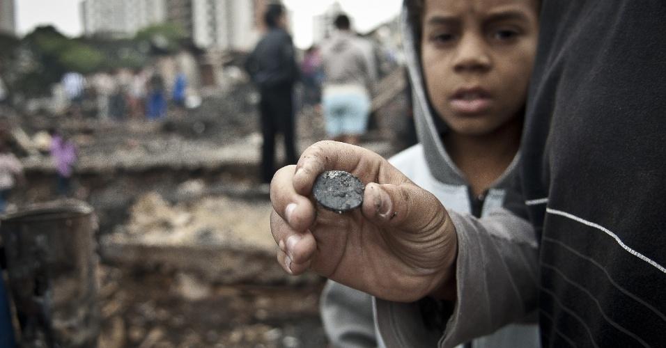 4.set.2012 - Criança exibe moeda encontrada em meio aos escombros na comunidade Sônia Ribeiro, conhecida como favela do Piolho (SP), que foi atingida por um incêndio na tarde de segunda-feira (3)