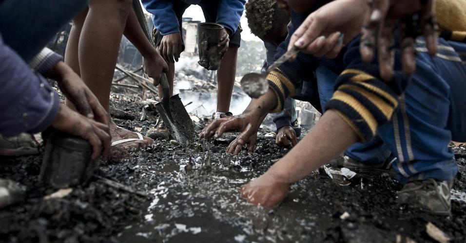4.set.2012 - Crianças procuram por moedas e pedaços de metal na comunidade Sônia Ribeiro, conhecida como favela do Piolho (SP), que foi atingida por um incêndio na tarde de segunda-feira (3)