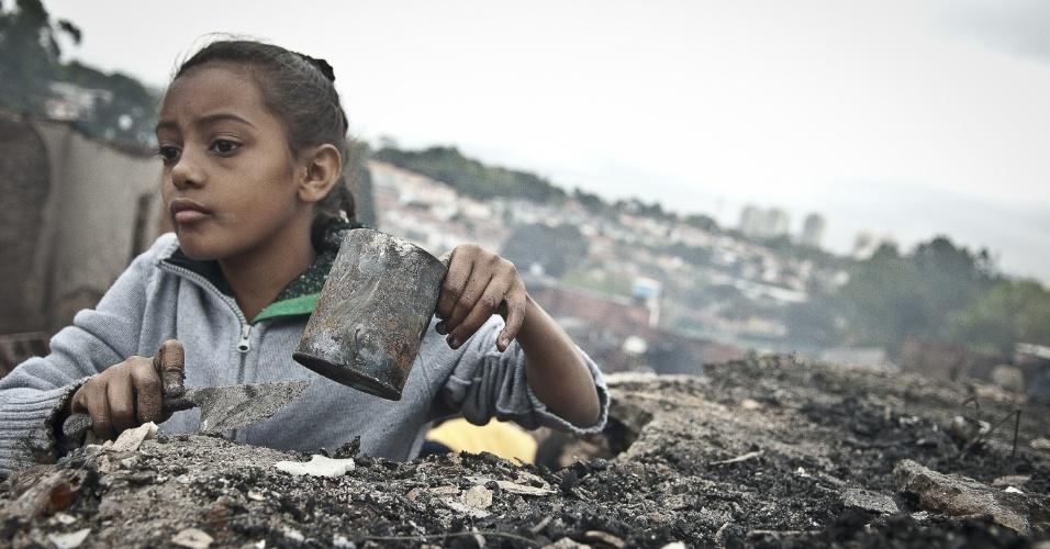 4.set.2012 - Menina procura por moedas e pedaços de metal na comunidade Sônia Ribeiro, conhecida como favela do Piolho (SP), que foi atingida por um incêndio na tarde de segunda-feira (3)