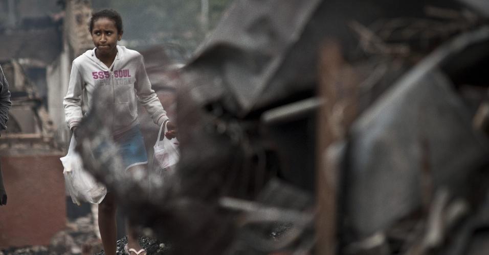 4.set.2012 - Moradora caminha em meio aos destroços e as cinzas dos barracos da comunidade Sônia Ribeiro, conhecida como favela do Piolho (SP), atingida por um incêndio na tarde de segunda-feira (3)