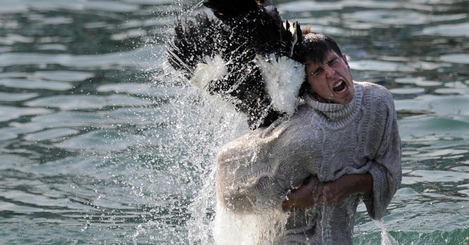 """5.set.2012 - Competidor agarra o pescoço de um ganso em Lekeitio, no norte da Espanha, durante a celebração do """"Antzar Eguna"""" (Dia do  Ganso). Na disputa, os espanhóis têm de agarrar o animal pelo maior tempo possível  ao ser mergulhado no mar"""