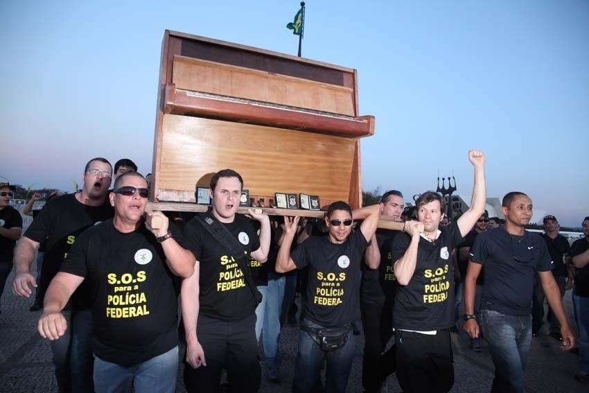 5.set.2012 - Em proteto, policiais federais carregam piano nas costas na Praça dos Três Poderes, em Brasília. A categoria continua de greve