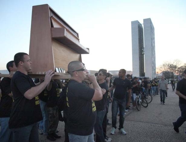 5.set.2012 - Policiais federais carregam piano nas costas durante passeata realizada na Praça dos Três Poderes, em Brasília. A categoria continua de greve