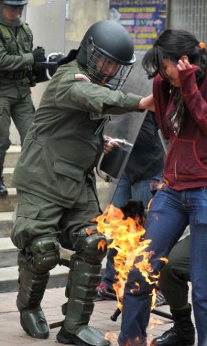 Policiais ajudam estudante que teria sido atingida por uma bomba caseira jogada por outros manisfestantes durante protesto pelas ruas de Bogotá, na Colômbia, contra a proposta de reforma do sistema público de educação