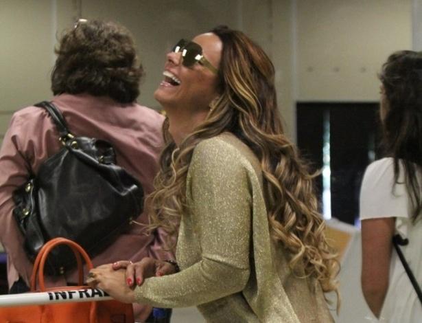 Viviane Araújo sorri enquanto aguarda para pegar suas malas, no desembarque no Rio de Janeiro (6/9/12)