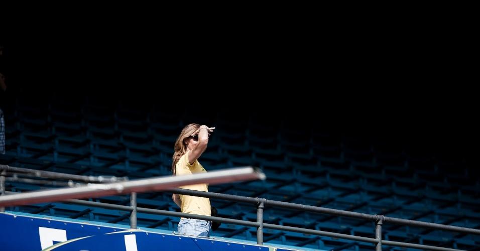Com estádio ainda vazio, torcedora usa óculos escuros para se proteger do sol