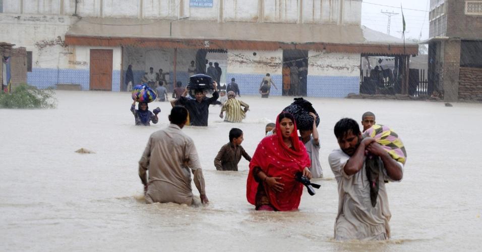 10.set.2012 - Família caminha nesta segunda-feira (10) por rua alagada na cidade de Jafarabad, no Paquistão. Chuvas de monções mataram ao menos 69 pessoas e deixaram centenas de desalojados no país