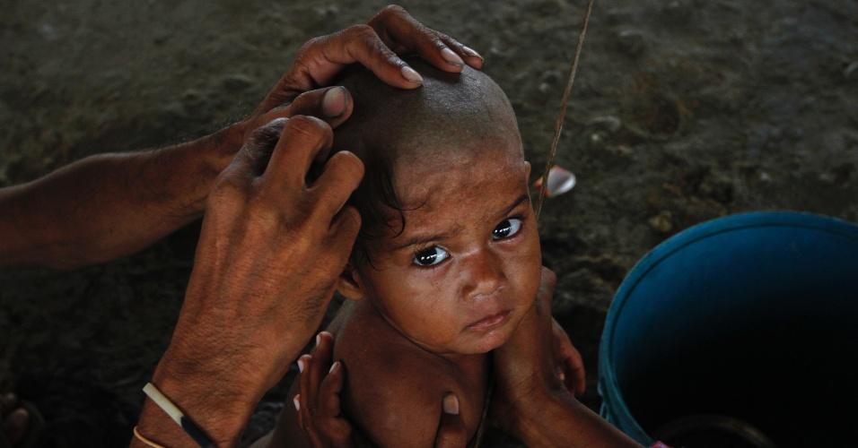 11.set.2012 - Homem raspa a cabeça de seu filho de apenas um ano de idade nesta terça-feira (11) em uma tenda onde sua família mora, em rodovia de Karachi, no Paquistão