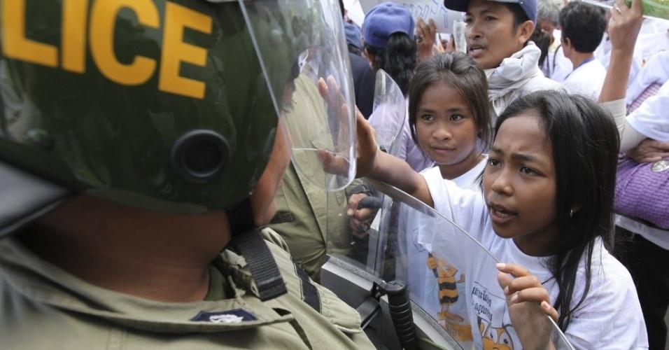 11.set.2012 - Menina se aproxima de policial durante protesto no Camboja nesta terça-feira (11). Centenas de pessoas se reuniram para protestar a favor da libertação do dono da emissora de rádio Beehive, Mam Sonando, que foi preso acusado de oposição