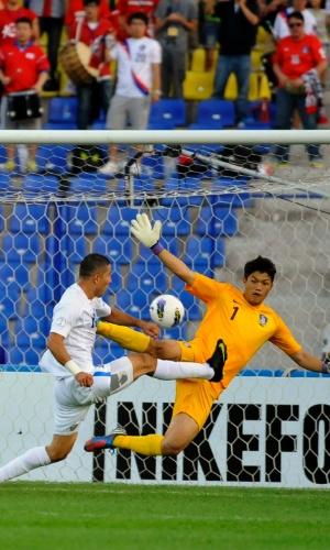 11.set.2012 - Bakaev (esq.), do Uzbequistão, tenta finalizar ao gol de Sungryong, goleiro da Coreia do Sul, em partida das eliminatórias da Copa-2014