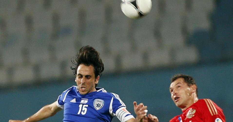 11.set.2012 - Yossi Benayoun (e), capitão de Israel, sobe para cabecear bola ao lado do russo Sergei Ignashevich em partida pelas eliminatórias da Copa-2014