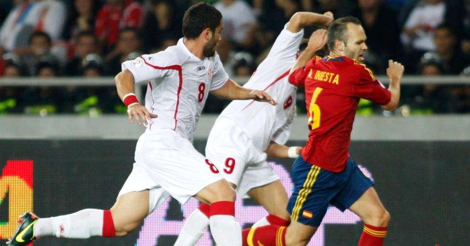 O espanhol Andrés Iniesta passa por entre dois georgianos em jogada individual feita no primeiro tempo da partida entre Geórgia e Espanha, em Tbilisi