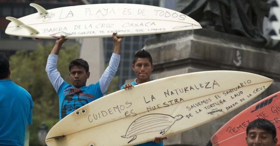 12.set.2012 - Surfistas de Oaxaca usam pranchas como cartazes de protesto contra a petrolífera Pemex na Cidade do México, nesta quarta-feira (12). Organizações ambientais acusam a morte de pelo menos 12 tartarugas em decorrência de 18 mil litros de óleo de uma refinaria da empresa em Salinas Cruz, no Estado de Oaxaca, no mês passado