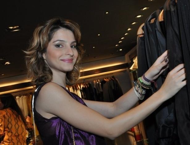 """A atriz Giselle Batista, de """"Cheias de Charme"""", olha roupas e sorri aos fotógrafos durante o evento (12/9/12)"""