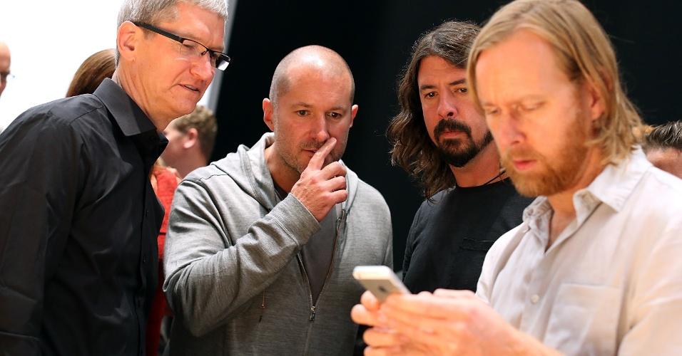 O CEO da Apple, Tim Cook (esq.), e o vice-presidente de design industrial da Apple, Jonathan Ive, ao lado de membros da banda Foo Fighters, que se apresentou no evento de lançamento do iPhone 5