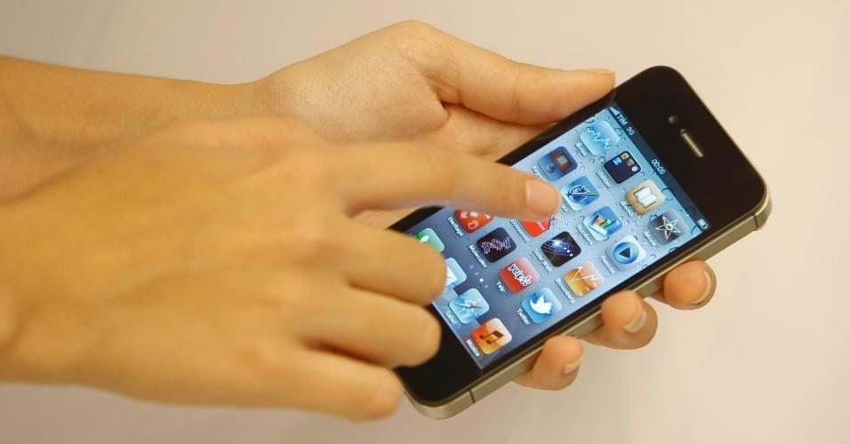 Usuário manuseia iPhone 4S em evento de lançamento do aparelho no Brasil