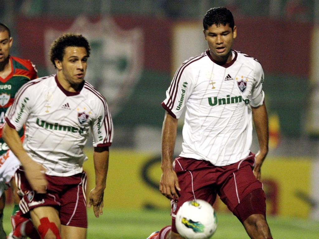 Wellington Nem corre atrás da bola observado por Gum e por jogador da Portuguesa