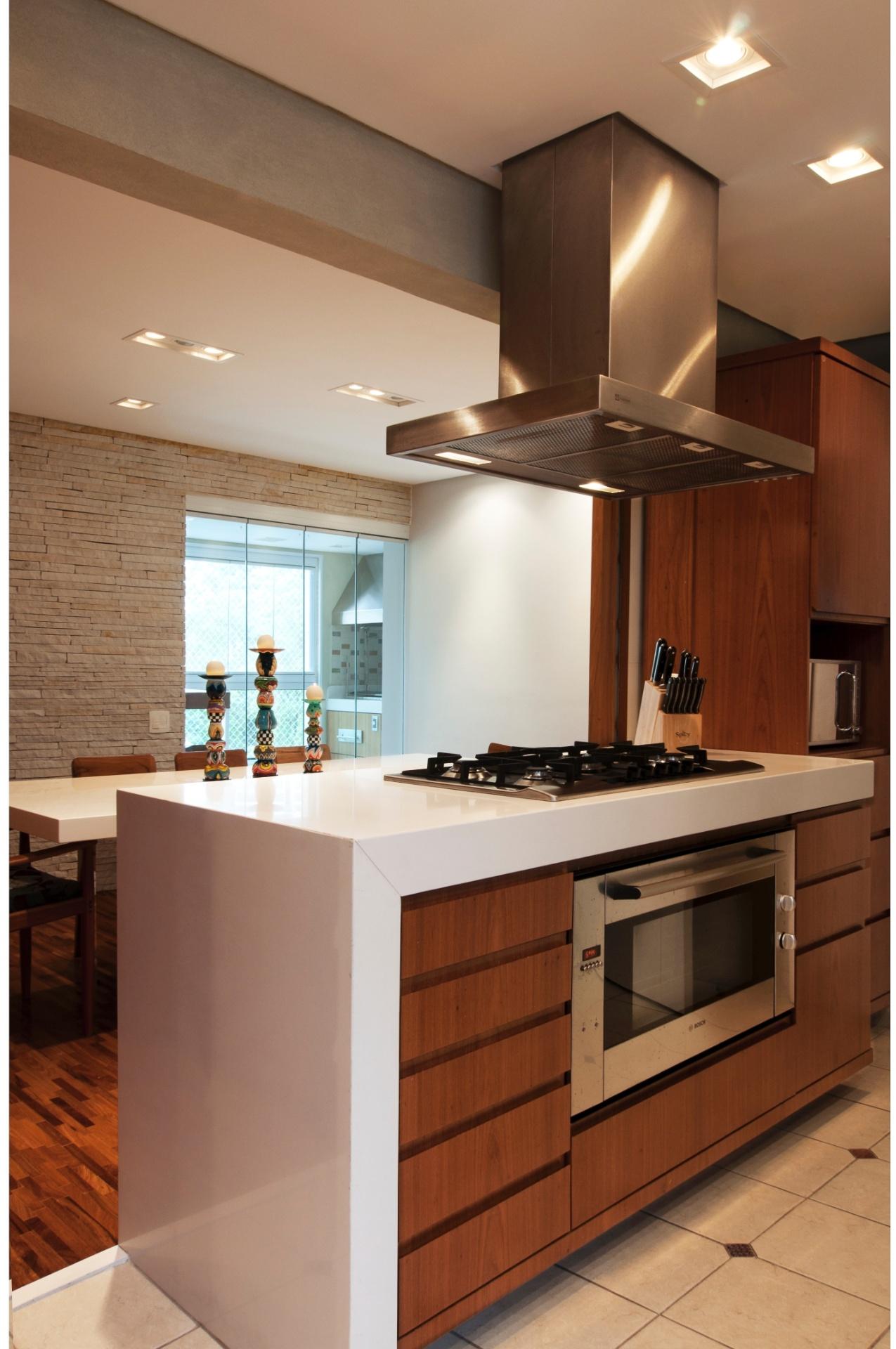 A bancada da cozinha para cooktop é feita com Silestone no tom branco Zeus - escolhido por se assemelhar ao brilho da mesa de jantar, mas assegurar grande resistência. Ao fundo, no jantar, a parede de canjiquinha mineira (Amazonas Pedras) separa o ambiente da área de churrasqueira acessível por uma porta de vidro. O projeto do apartamento Itapaiuna II é assinado por Crisa Santos