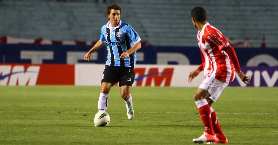 Elano, meia do Grêmio, conduz a bola no meio campo e é observado por jogador do Náutico