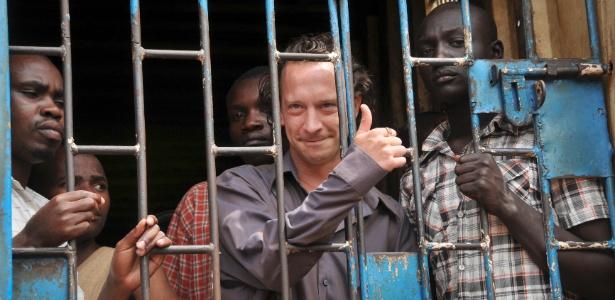 O cineasta David Cecil faz sinal para fotógrafos da cela onde está preso, em Kampala, Uganda (13/9/12)