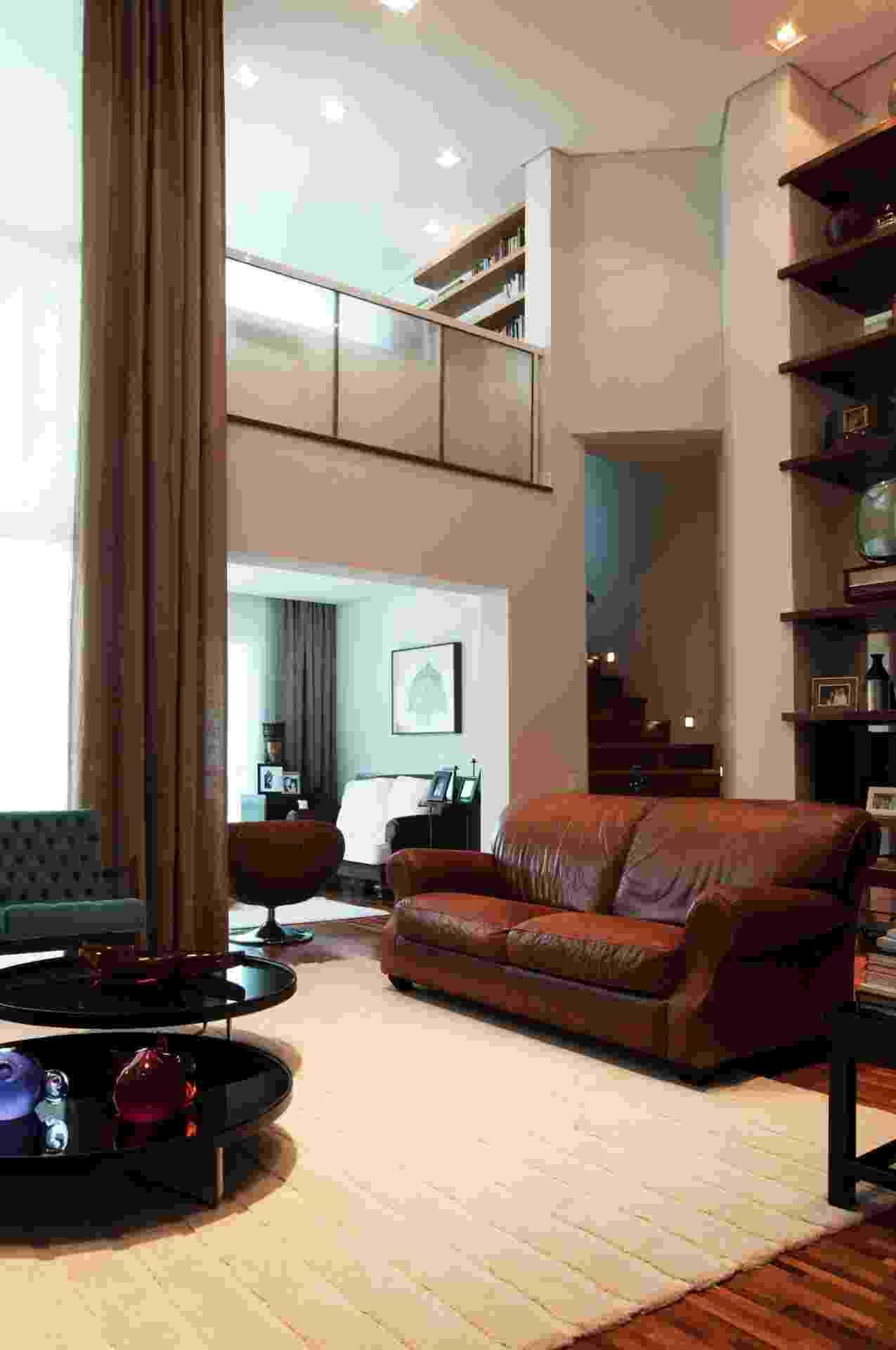 O sofá de couro é norte-americano - herança de avós - e foi escolhido para compor a sala do apartamento Itapaiuna II, projetado por Crisa Santos. Por ser liso, o móvel fica de frente para a parede repleta de máscaras, realçada por um segundo sofá revestido em veludo étnico. As duas mesas de centro (Dpot) são pretas e, nos fundos (à dir.), há uma escada leva ao escritório do mezanino. No mesmo nível do living, uma sala de leitura é separada deste ambiente por uma cadeira oval giratória (Saccaro) - Luxas Fonseca/ Divulgação