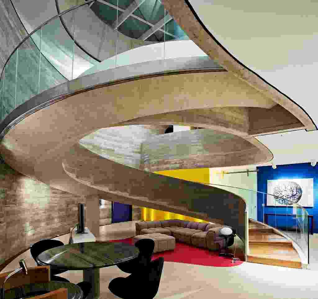 A arquitetura de Ruy Ohtake tem seu ponto alto nesse espaço onde estão home theater, lounge e bar. Dele uma rampa-escada escultórica liga o térreo ao pavimento superior, onde estão os dormitórios. Sobre a escadaria, uma clarabóia com 4,50 m de diâmetro favorece a iluminação farta e realça o contraste de materiais: concreto, vidro e madeira, todos em quantidade abundante na Casa Valinhos - Daniel Ducci/ UOL