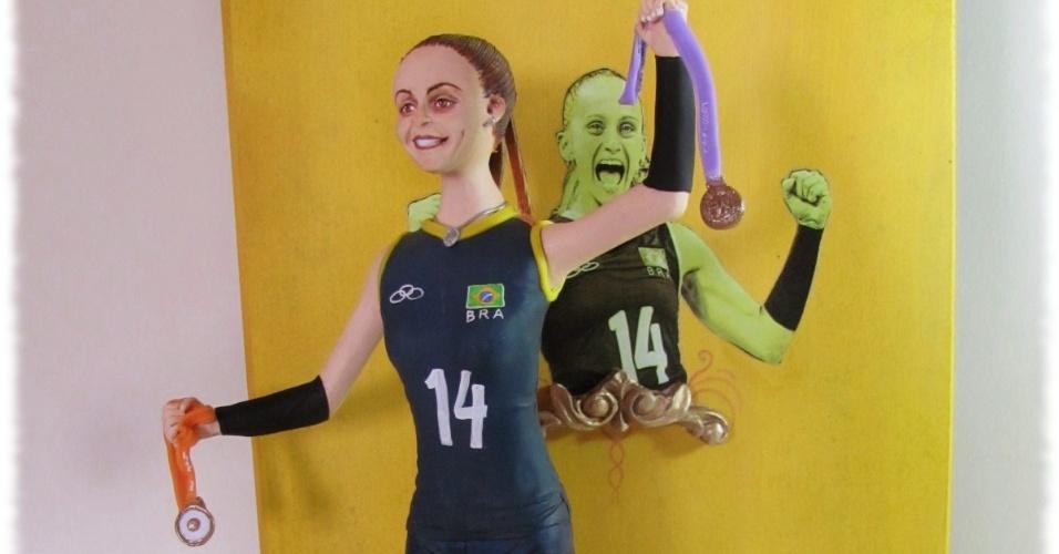 A caixa que guarda a boneca é verde, laranja e amarela e traz um retrato de Fabi comemorando um ponto