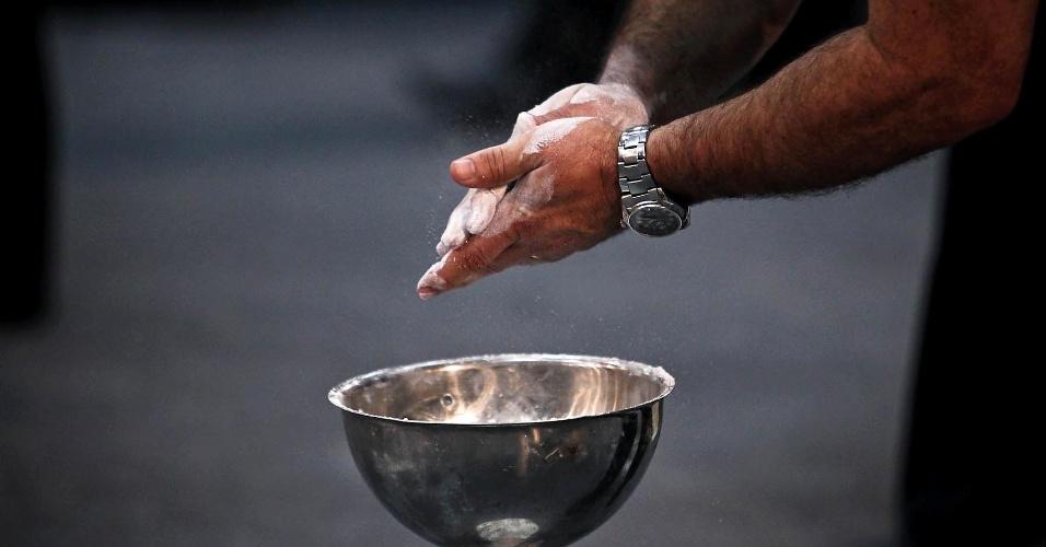 Competidor passa pó branco nas mãos para se preparar para duelo e evitar que as mãos escorreguem