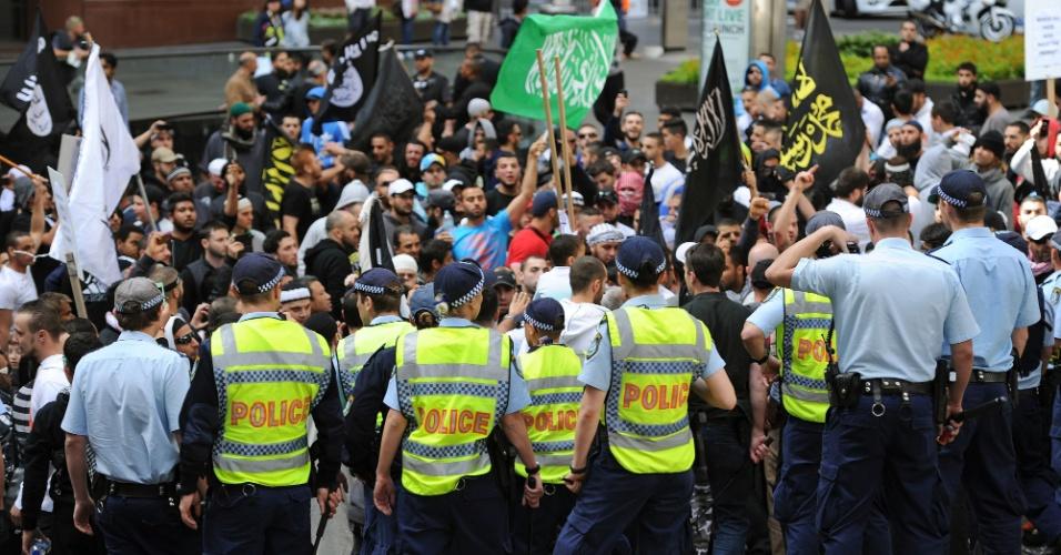 15.set.2012 - Policiais vigiam manifestantes próximo ao consulado dos EUA no centro de Sydney (Austrália), neste sábado (15)