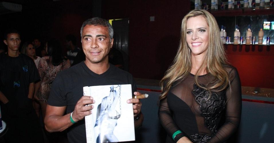 A capa da playboy do mês de setembro, Denise Rocha, assina um exemplar para Romário na festa de lançamento da revista em boate do Rio de Janeiro (13/9/12)