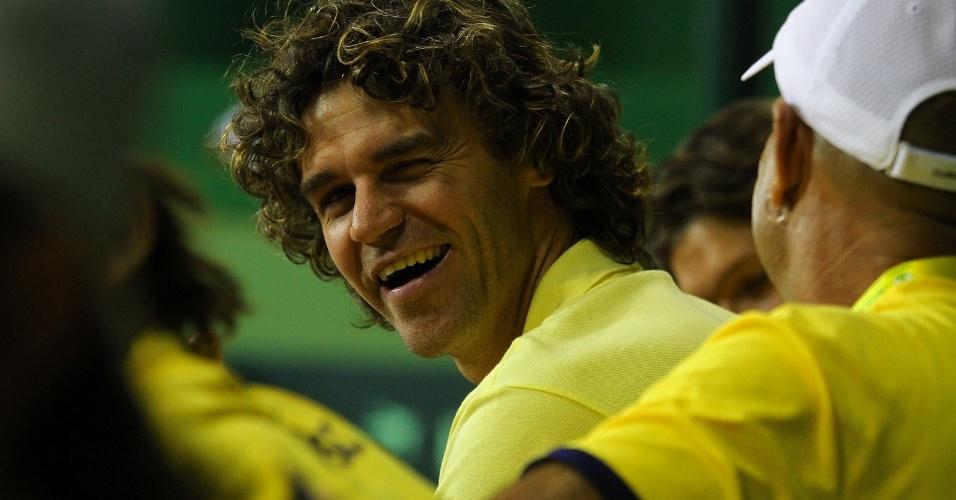 Gustavo Kuerten sorri enquanto assiste à vitória de Bellucci junto com a equipe brasileira na Davis