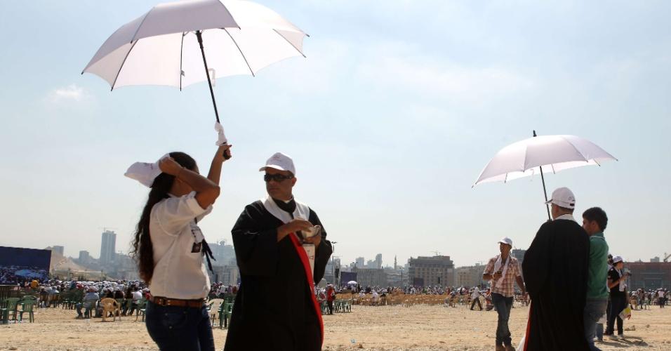 15.set.2012 - Padres libaneses se protegem com guarda-chuvas para dar a hóstia aos fiéis durante missa celebrada pelo papa Bento 16 em Beirute, no Líbano