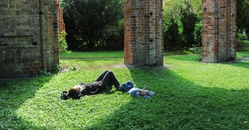 16.set.2012 - Ao lado do filho, mulher descansa em jardim perto de monastério nos arredores de Oldenburg, no oeste da Alemanha, neste domingo