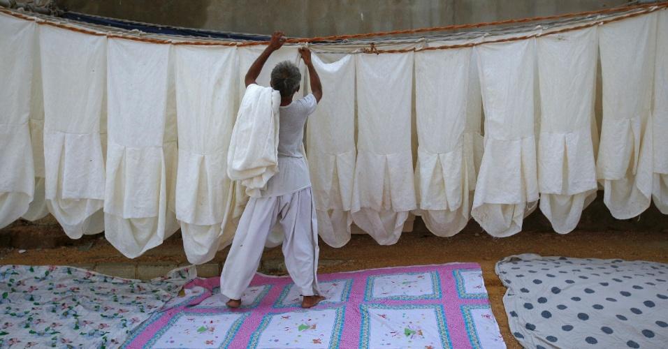 16.set.2012 - Homem estende roupas em varal improvisado ao longo de uma rua na periferia de Karachi, no Paquistão