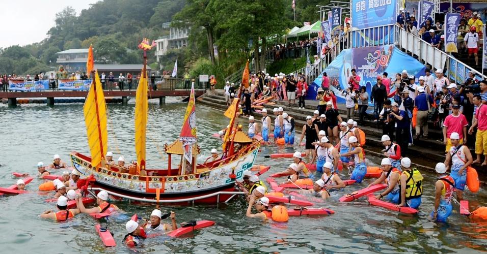 16.set.2012 - Imagem da deusa Matsu, a bordo de um barco de madeira, é cercada por nadadores, na ilha de Sun Moon Lake, em Nantou, Taiwan. Cerca de 28 mil nadadores participaram do evento e percorreram uma distância de 3,3 km em homenagem à deusa